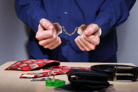Businessman with handcuffs, stripped of personal items during arrest Stock Photo