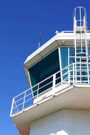Part of aerodrome control tower with ladder, against clear sky