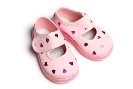 Pair of pink baby shoes with reflective hearts, on white background