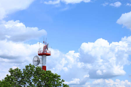 Air traffic control communications tower against cloudy blue sky, symbolic background Stock Photo