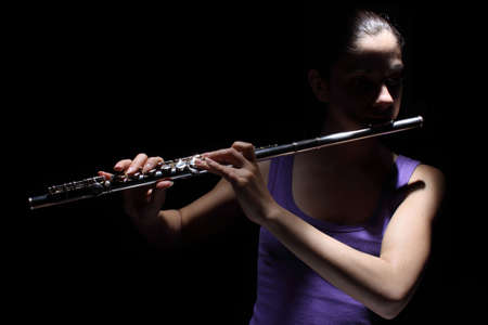 Girl in lavender shirt playing a flute in the spotlight