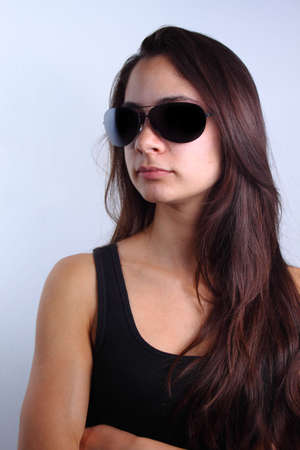 Portrait of a beautiful young woman with long brown hair wearing black shirt and sunglasses