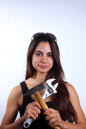 Beautiful young woman with long brown hair wearing black shirt and sunglasses and holding tools Stock Photo