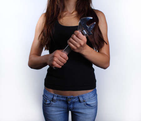 Fit young woman in black shirt and blue jeans, holding big wrench Stock Photo