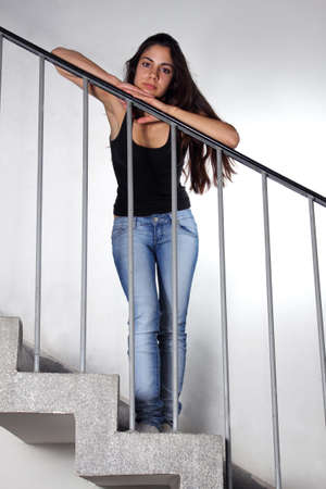 Beautiful young woman leaning on staircase railing