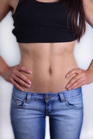 flat stomach: Bella giovane donna che mostra il suo stomaco piatto