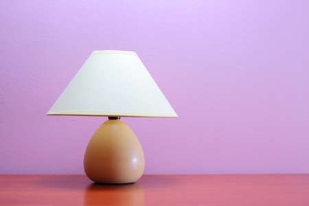 Lamp on a wooden table against purple wall