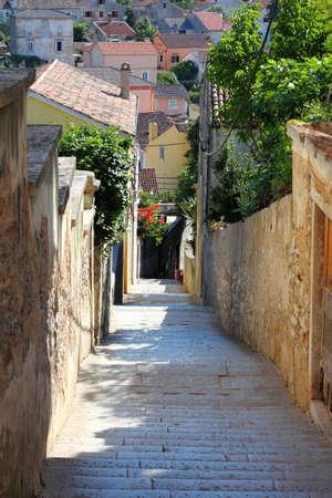 View down a narrow stone-paved street in Mali Losinj, Croatia Stock Photo