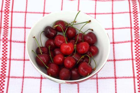 Bowl of fresh cherries on dishcloth
