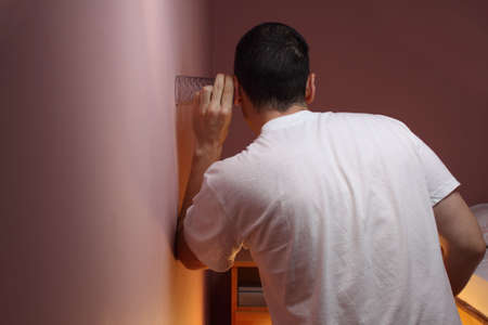 Man eavesdropping through a bedroom wall using a glass
