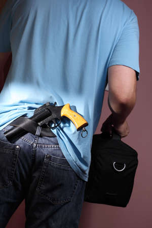 Man with handgun tucked in belt leaving room carrying black bag photo