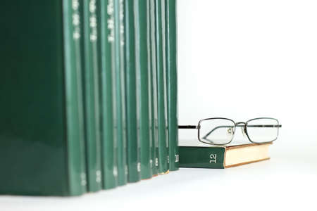 Row of green books and reading glasses resting on top of last book