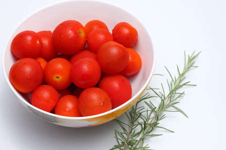 Bowl of red cherry tomatoes and some rosemary