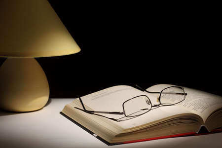 Reading glasses resting on top of open book next to night lamp Stock Photo - 7520970