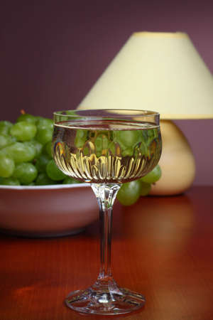 Glass of white wine on wooden table with bowl of grapes and table lamp Stock Photo