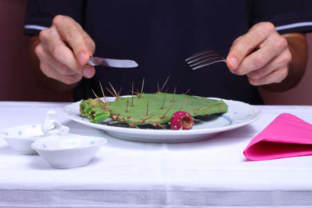 Man eating cactus in a restaurant, unhealthy eating concept