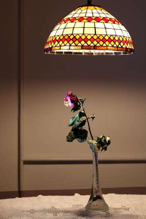flores secas: Una rosa seco en florero de vidrio bajo luz colgante
