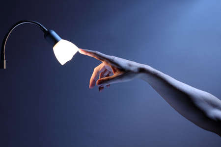 Hand touching lamp with index finger, energy and environment concept