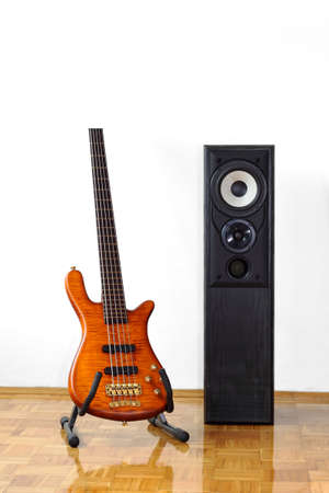 Five string electric bass guitar on a stand next to a floor-standing loudspeaker Stock Photo