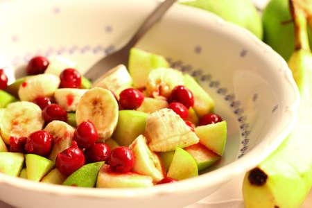 White ceramic bowl full of fruit, bananas, apples, sour cherries