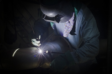 A man with personal protective equipment is doing welding in low light area Фото со стока