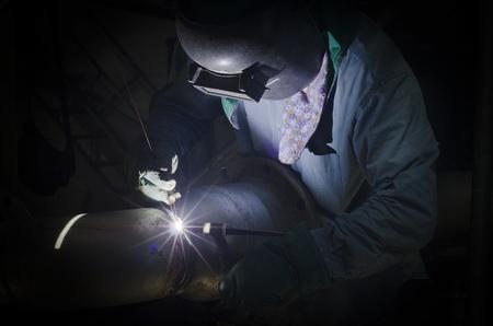Een man met persoonlijke beschermingsmiddelen aan het doen is lassen bij weinig licht gebied