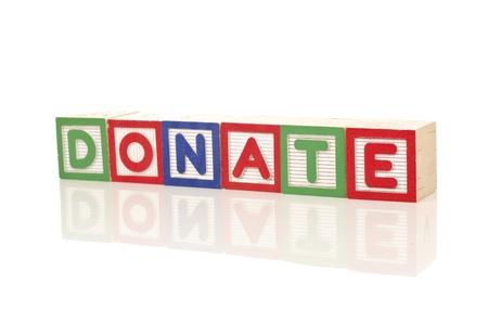 doneren woord over de kleurrijke houten blokken op een witte achtergrond Stockfoto