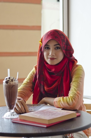 beautiful young muslim woman with lovely smiles having lunch at coffee shop photo