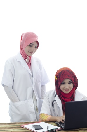 beautiful muslim medical doctors woman working with computer isolated on white background photo