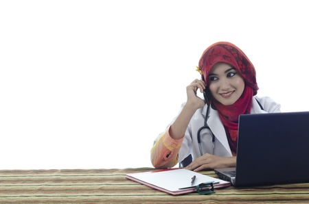 beautiful young muslim woman doctor with stylish head scarf make a phone call in front of laptop isolated on white background photo