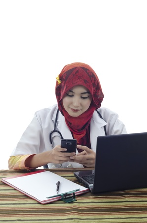 beautiful muslim medical doctor woman with stylish scarf using phone isolated on white background photo