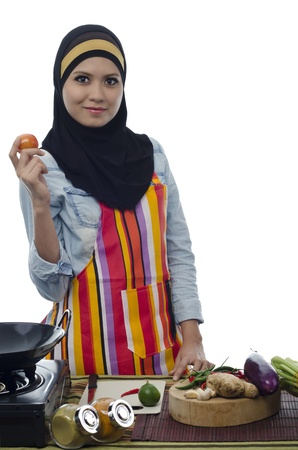 Beautiful muslim woman holding tomato and prepare for cooking healthy food in the kitchen Stock Photo - 11904900