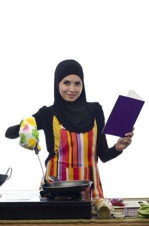 Mooie moslim vrouw met kookboek tijdens het koken gezond voedsel in de keuken Stockfoto