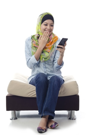 Beautiful muslim woman shocked and happy when got good news from somebody send message using phone Stock Photo