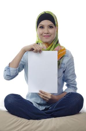 Mooie jonge moslim vrouw stoel en met een blanco papier
