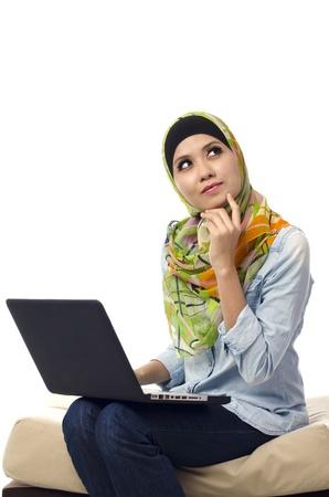 Mooie moslima zit in de voorkant van laptop en denken Stockfoto