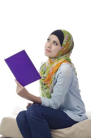 Mooie jonge moslim vrouw lezen en denken