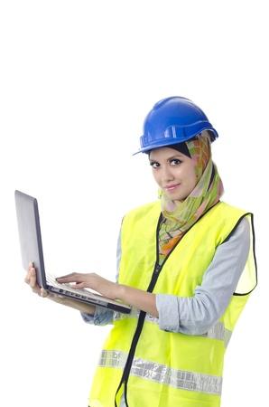 personal protective equipment: Beautiful muslim woman with personal protective equipment holding laptop
