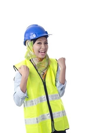 Happy muslim woman wearing safety helmet with excited expression isolated white background. Her both hand up at her waist. photo