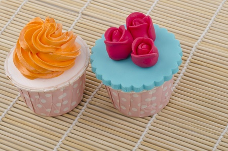 two colorful cupcakes on bamboo mat photo