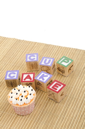 colorfull cup cake with wood blocks on bamboo mat