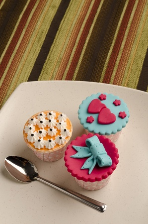 Colorfull cup cakes with spoon  on white plate isolate stripe background