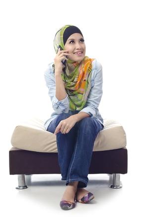 mooie jonge moslim meisje genieten van haar gesprek met vrienden met telefoon geà ¯ soleerd op witte achtergrond