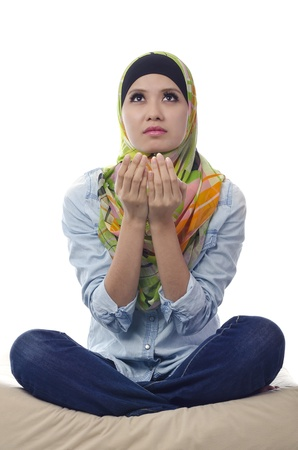 Pretty young Asian Muslim woman praying in action. photo