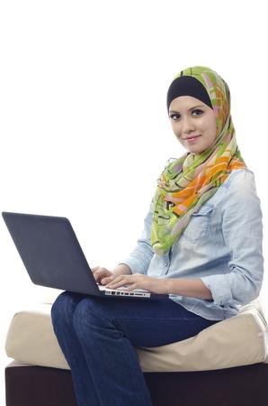 Mooie moslim vrouw glimlachend praatje met haar vrienden met behulp van computer Stockfoto