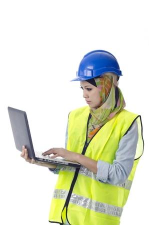 Mooie moslima met persoonlijke beschermingsmiddelen kijkt uit op de computer Stockfoto