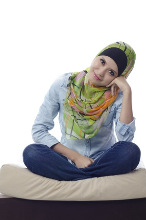 beautiful muslim woman with stylish head scarf sitting with cross-legged on a couch
