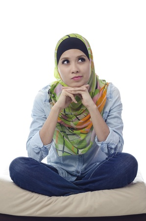 beautiful muslim woman sitting with cross-legged on a couch and thinking for someone photo