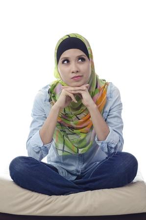mooie moslim vrouw zit met gekruiste benen op een bank en denken voor iemand Stockfoto