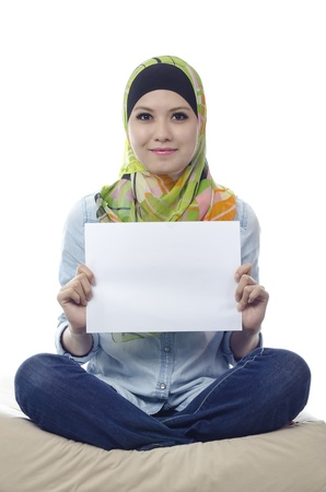 Beautiful young muslim woman seat and holding a blank paper photo